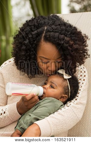 African American woman feeding her daughter with a bottle.