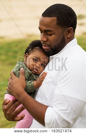 African American loving father holding his daughter.