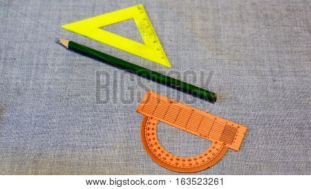 Set of plastic rulers and a protractor between the pencil