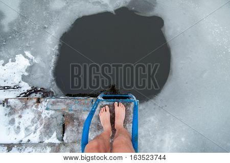 Men Is Legs On The Ice Near The Ice Hole