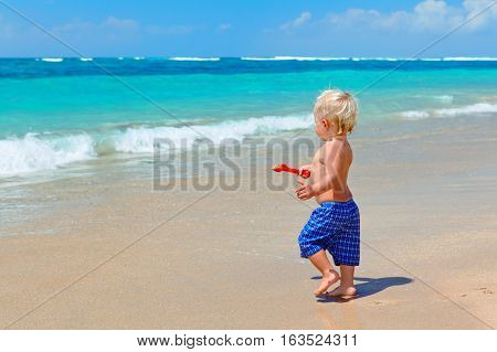 Funny photo of happy baby boy playing game with sand and water running to ocean surf for swimming. Family travel lifestyle recreation water outdoor activity on summer beach vacation with children