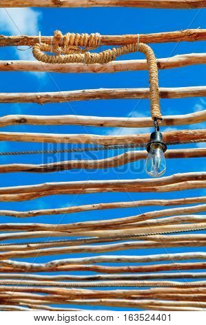 Retro style interior background . Decorative rough wood sticks shed with vintage design lamp and natural rope decoration on blue sky background.