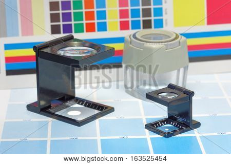 Three magnifier or printer's loupe sits on a cyan test sheet in a pre-press workshop
