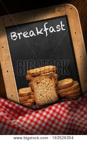 Rusks of wholemeal flour in a blackboard with text Breakfast. On a table with red and white checkered tablecloth
