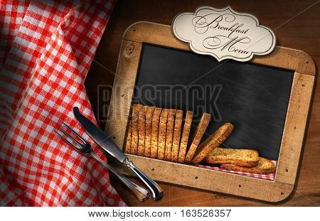 Rusks of wholemeal flour in a blackboard with a label with text Breakfast Menu. On a table with a checkered tablecloth and silver cutlery