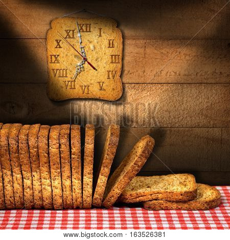 Rusks of wholemeal flour on a table with red and white checkered tablecloth with a clock made with a rusk. Concept of time for a healthy breakfast