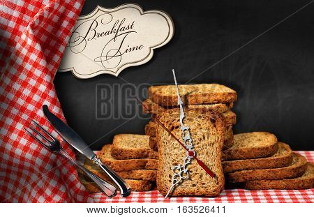 Rusks on a table with a clock made with a rusk silver cutlery and a label with text Breakfast time