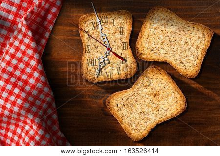Three healthy rusks of wholemeal flour with a clock made with a rusk. Concept of time for a healthy breakfast