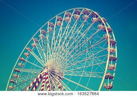circular big ferris wheel on blue sky background vintage filtered image