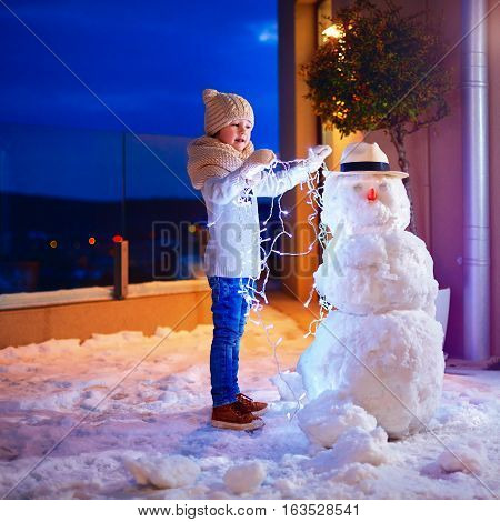 Young Kid Making Snowman In Backyard In The Twilight