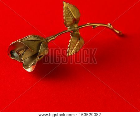 One Metal Rose On A Red Background For Holiday Greetings