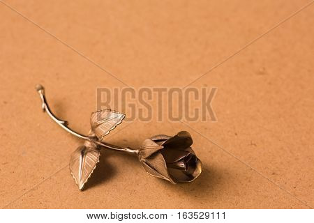 One Metal Rose On A Beige Background For Holiday Greetings