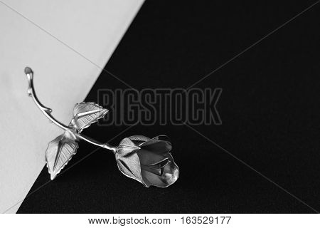 One Metal Rose Lays On A Black And White Background.