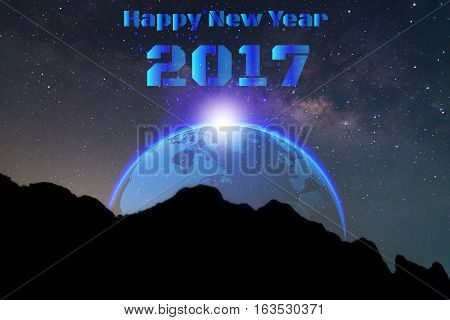 Milky way and silhouette of mountain with globe and text happy new year 2017