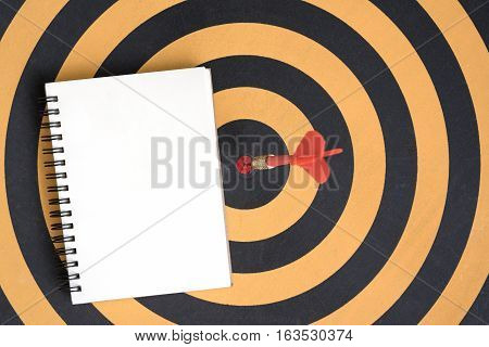 Arrow hitting in bullseye target on dartboard with open spiral notebook