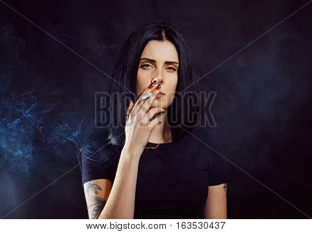 Seductive young girl smoking over dark background