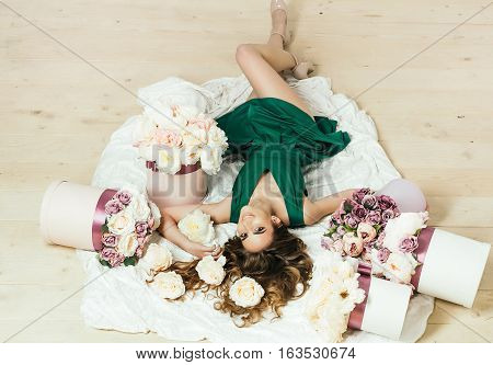 Sexy young pretty woman or cute smiling girl with long hair in green dress laying on white bedsheet among lilac rose and peony flowers on wooden floor