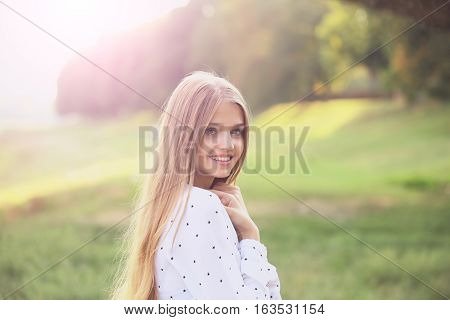 Pretty  cute young woman or girl with long blonde hair tender hands in white blouse with stars smiling in sunny summer day on natural background