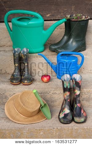 Gardening Tool Of Watering Can Rubber Boots Wicker Hat Shovel And Red Apple On Rung Outdoor Close Up.