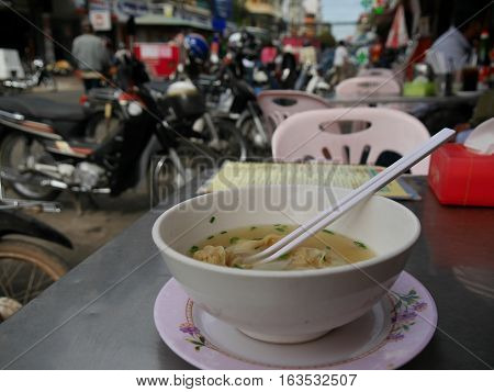 Wan Tan soup in white bowl with motorbikes and street scene in background