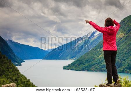 Travel concept. Tourist woman looking and pointing with finger at fjords beautiful mountains landscape in Norway