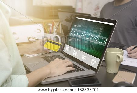 business hand typing on computer keyboard with credit card and Economics homepage on the computer screen business freelance concept.