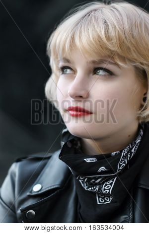 Thoughtful blonde short haired woman portrait in the street
