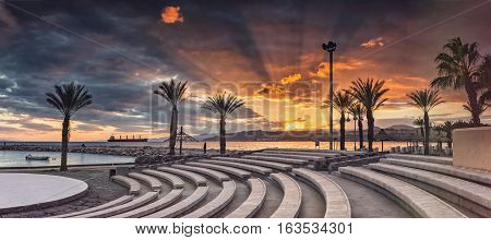 Colorful sunset at the Red Sea; view from stone amphitheatre on central beach of Eilat - famous resort and recreational city in Israel
