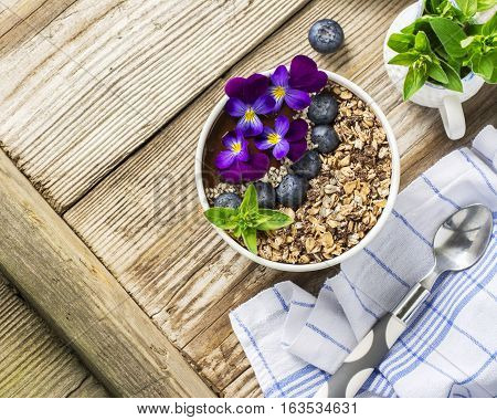 Chocolate Banana Smoothies Bowl with a topping of granola, blueberries, white sesame decorated with flowers purple garden viola on a simple wooden background. The concept of healthy organic breakfast