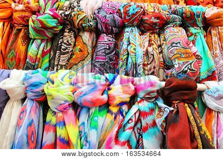 Rows of colourful silk scarfs hanging at a market stall in Tossa de Mar, Spaine