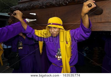 Antigua Guatemala - April 16 2014: Young man wearing a purple and yellow robe carrying a float (anda) during the Easter celebrations in the Holy Week in Antigua Guatemala.
