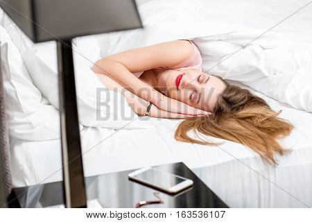 Beautiful young woman waking up in the bed at the morning. Good morning concept