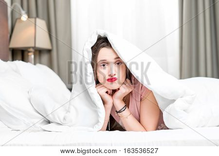 Portrait of young sad woman hidding under the white sheets on the bed