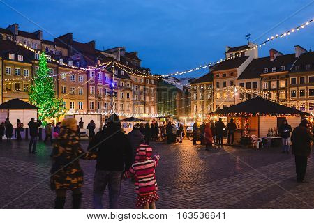 Warsaw, Poland - December 25th, 2016. Winter market and xmas tree with festive decoration surrounded by historical buildings on the Old town square by Christmas night.