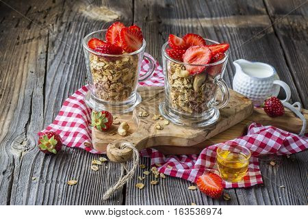 Healthy breakfast for two. Home baked granola with honey and cashews. In a tall glass with slices of strawberry. selective focus