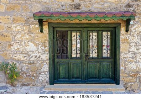 Green Wooden Door With Wrought Iron Of A Stone Building