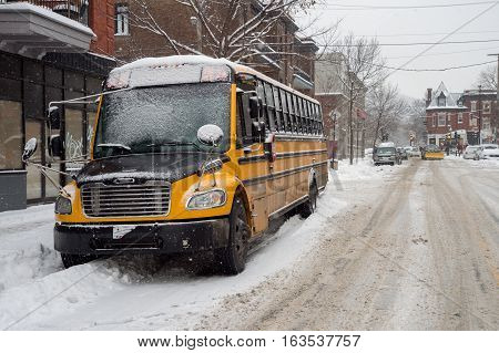 Montreal CA - 12 December 2016: Yellow school bus parked in Mile End neighborhood during Snowstorm