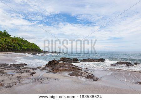 Waves crashing to rocks montezuma beach Costa Rica