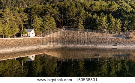 Small house and trees reflected on the damn. Prodormos Dam Troodos Cyprus.