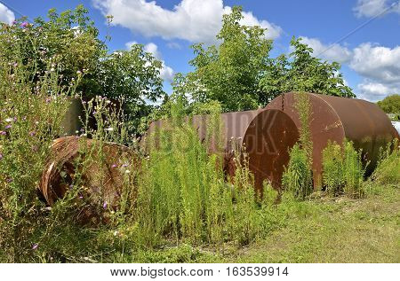 A row of old rusty metal storage tanks and barrels.are left in the weeds and shrubs