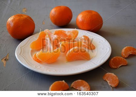 Mandarines, peeled tangerine and tangerine slices on a  wooden table