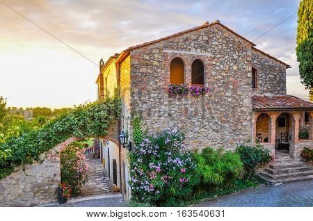 Beautiful old Itanlian stone house with arched windows and typical plants during sunset, Banjo di Gavorano, Italy