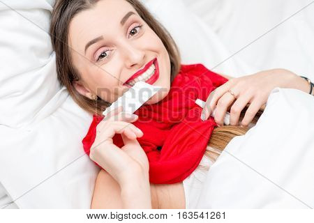 Young woman ill with cold lying on the bed with red scarf and pills