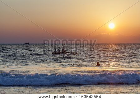 Fishermen move off in searches of a catch by the traditional old fishing boat against the background of a sunset.