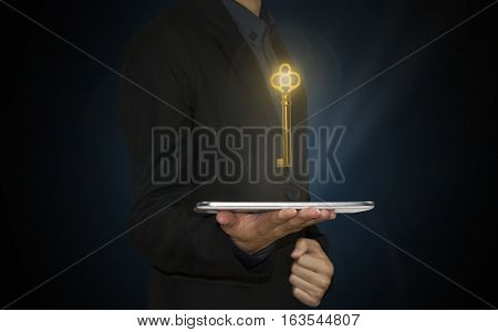 businessman hand holding tablet with gold key. concept unlock business success.