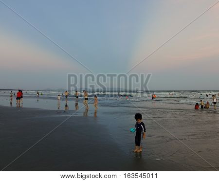 People Playing On The Beach At Sunset