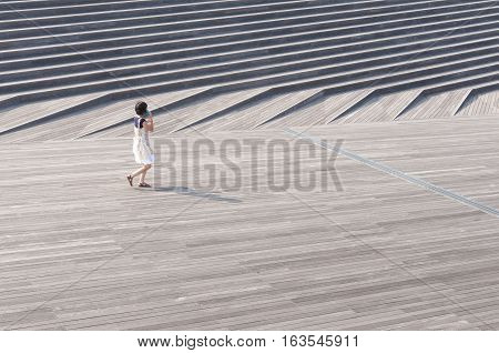 sunny day at famous Osanbashi pier in Yokohama with unidentified woman walking by deck
