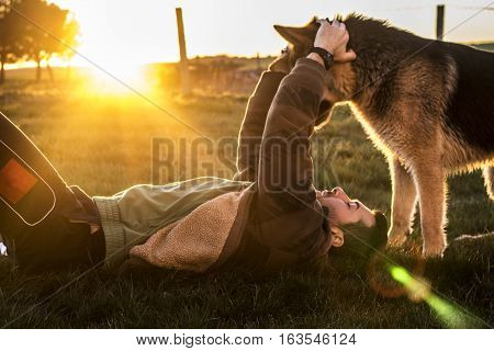 Young boy playing with a dog at sunset