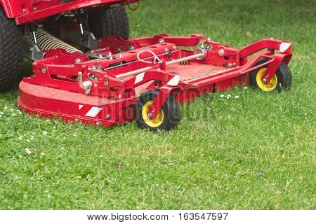 Lawnmower cuts a green garden grass closeup
