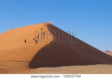 Namib-Naukluft National Park, Namibia - August 2016: Visitors walking up Dunes 45